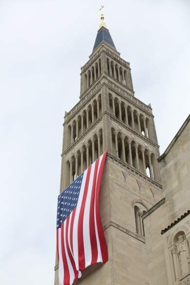 A large American flag is seen hanging from the bell tower of the Basilica of the National Shrine of the Immaculate Conception in Washington last July 4. The U.S. bishops' fifth annual Fortnight for Freedom opens June 21. (CNS/Bob Roller)