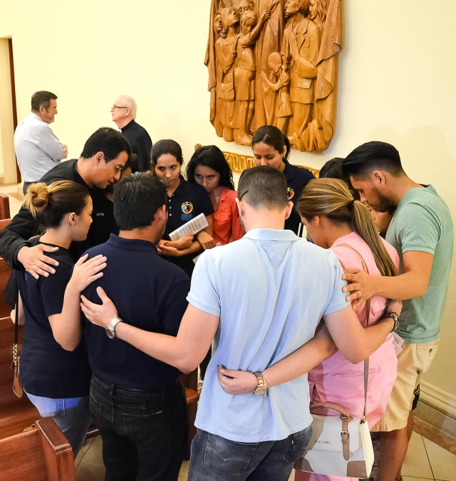 "Father Jorge Torres, director of vocations for the Diocese of Orlando, Fla., prays with young people who participated in the ""Vigil to Dry Tears"" June 13 at St. James Cathedral in Orlando. Father Torres is among the Orlando diocesan priests lending a hand in counseling families and friends of victims of the June 12 massacre at Pulse nightclub in Orlando. (CNS/Andrea Navarro, Florida Catholic)"
