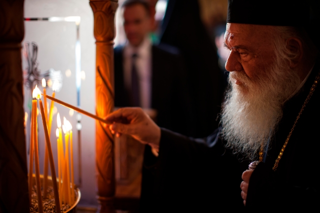 Orthodox Archbishop Ieronymos II of Athens and all of Greece lights a candle as he enters St. Mena Cathedral in Heraklion, Greece, June 19. The Great and Holy Council of the Orthodox Church opened June 19. Although intended to be the first council of all the Orthodox churches in more than a millennium, the gathering opened with the absence of representatives from four Orthodox churches. (CNS/Sean Hawkey)