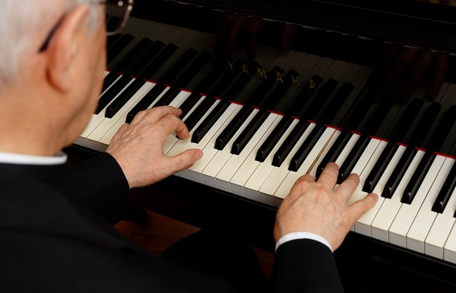 Cardinal Baldisseri plays the piano in his office at the Vatican. (CNS/Paul Haring)