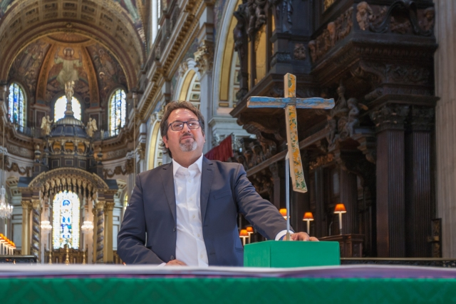Italian carpenter Francesco Tuccio is pictured in London's St. Paul's Cathedral with a cross he made from pieces of a boat that wrecked in 2013 off the coast of Lampedusa, Italy. The British Museum commissioned the weather-beaten cross displayed at the cathedral, and it now holds a prominent place in the museum in London. (CNS/Graham Lacdao, Chapter of St Paul's)