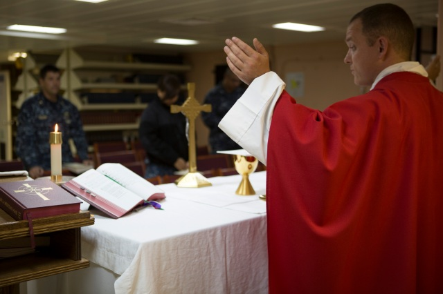 Father William J. Brunner, of the Diocese of Green Bay, Wis., celebrates Mass aboard the Navy warship USS America docked in San Diego. Father Brunner, who holds the rank of lieutenant, is one of the Navy's newest chaplains. (CNS/Chaz Muth)