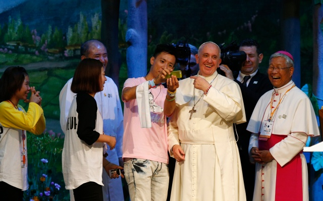 Pope Francis gestures as a young man takes a selfie during a meeting with Asian youth in South Korea in 2014. (CNS/Paul Haring)