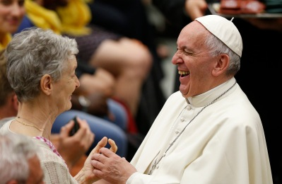 Pope Francis laughs as he greets a woman during a meeting in 2016. (CNS/Paul Haring)