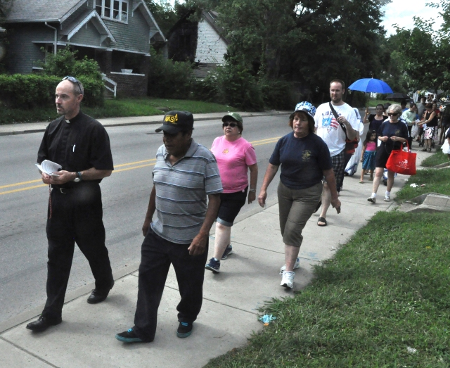Father Christopher Wadelton, pastor of St. Philip Neri Parish in Indianapolis, leads a group in praying the rosary July 10 while walking through the church's neighborhood. The parish was sponsoring a series of nine consecutive prayer walks in response to increased drug problems and violent crimes in its neighborhood. (CNS/Sean Gallagher, The Criterion)