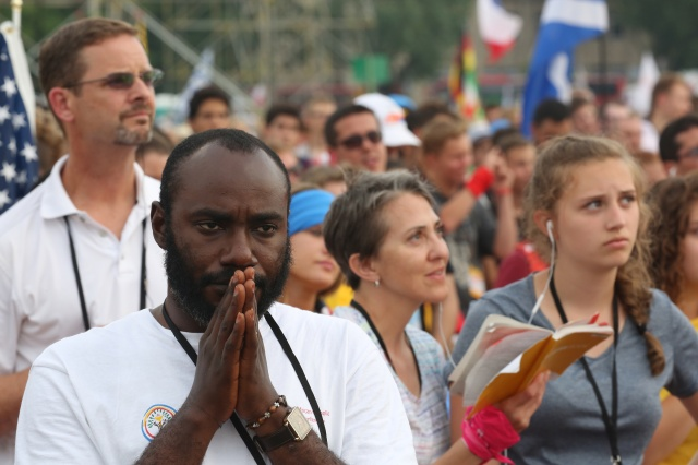 A pilgrim prays during the opening Mass for World Youth Day July 26 in Krakow. (CNS/Bob Roller)