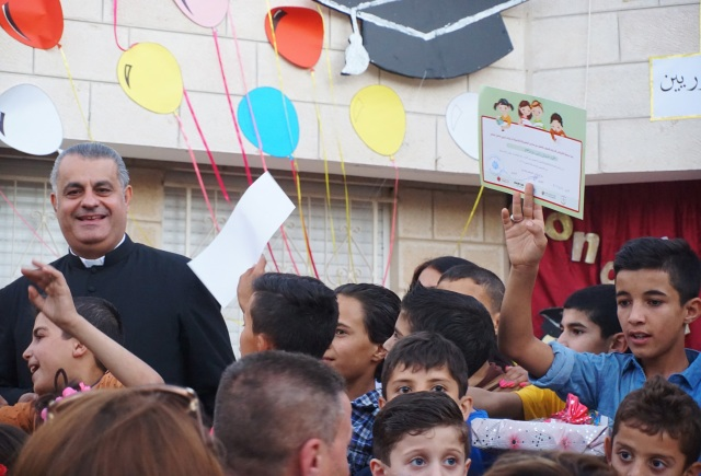 Father Rifat Bader celebrates with Syrian refugee children during a graduation ceremony at the Latin Patriarchate School in Naour, Jordan, July 11. (CNS photo/Dale Gavlak)