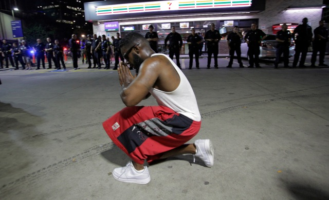 A protester prays near Dallas police officers July 7 after police officers were shot during a protest in Dallas. Snipers shot and killed five police officers and wounded seven more at the demonstration to protest the police killing of black men in Baton Rouge, La., and St. Paul, Minn. Two civilians also were injured in Dallas. (CNS photo/Ralph Lauer, EPA)