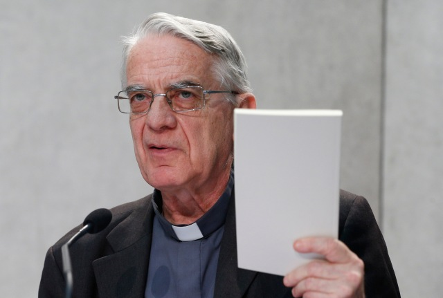 "Jesuit Father Federico Lombardi, who was then the papal spokesman, holds a copy of Pope Francis' apostolic exhortation on the family, ""Amoris Laetitia"" (""The Joy of Love""), during a news conference for its release at the Vatican April 8. The exhortation is the concluding document of the 2014 and 2015 synods of bishops on the family. (CNS/Paul Haring)"