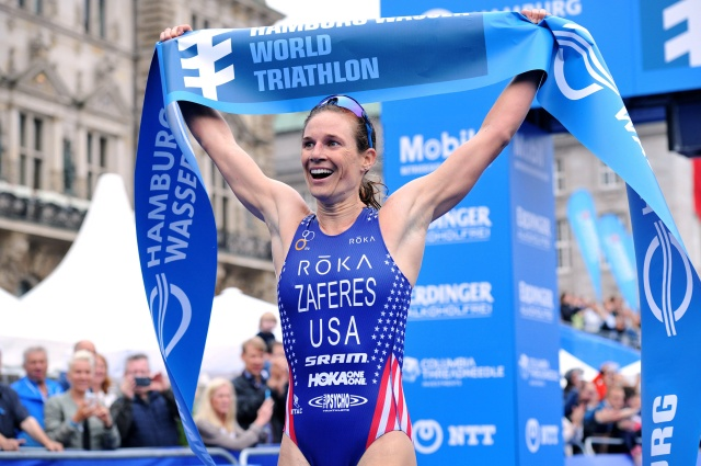 Triathlete Katie Hursey Zaferes raises a banner after winning the World Triathlon Series in Hamburg, Germany, July 16. (CNS/courtesy ITU via Catholic Review)