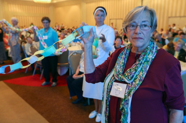 "Sister Meg Causey, a member of the Society of the Sacred Heart from Poughkeepsie, N.Y., right, stands with other sisters as they hold a ""chain of bondage."" Each link on the chain documents moments when an individual or her respective religious community was not welcomed to a person of color. (CNS/Michael Alexander, Georgia Bulletin)"