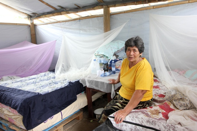 Alicia Nevares, 65, sits on a bed in the tent that she shares with other family members in the village of Bigua, Ecuador. Although reconstruction is under way, many families continue to live in tents provided by Catholic Relief Services and Caritas Internationalis. (CNS/Barbara Fraser)