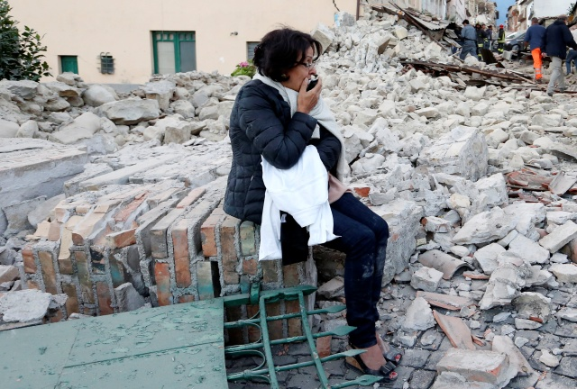 A woman sits amid rubble following an earthquake in Amatrice, Italy, Aug. 24. (CNS/Reuters)