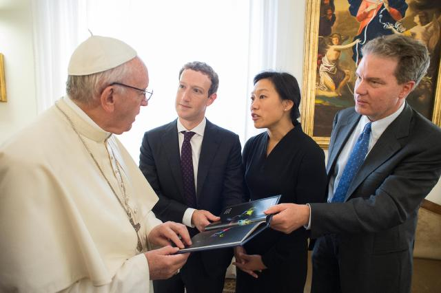Pope Francis accepts a book from Mark Zuckerberg, CEO of Facebook, who was accompanied by his wife, Priscilla Chan, during a private audience at the Vatican Aug. 29. At right is Greg Burke, director of the Vatican press office. (CNS/L'Osservatore Romano)