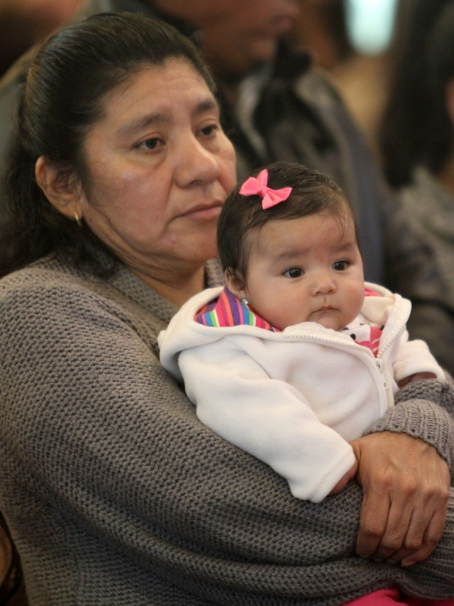 A woman holds a baby during a Spanish-language Mass honoring immigrants at St. John the Evangelist Church in Riverhead, N.Y., in 2011. (CNS photo/Gregory A. Shemitz)