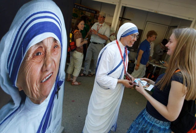 A member of the Missionaries of Charity talks with a pilgrim from Germany near an image of Blessed Mother Teresa of Kolkata during World Youth Day in Madrid in 2011. Members of religious orders and clergy were on hand during the international gathering to encourage youths to think about vocations. (CNS/Paul Haring)