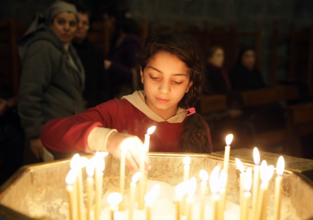 A young Christian worshipper lights a candle during a 2015 Mass for peace at a church in Damascus, Syria. (CNS/EPA)