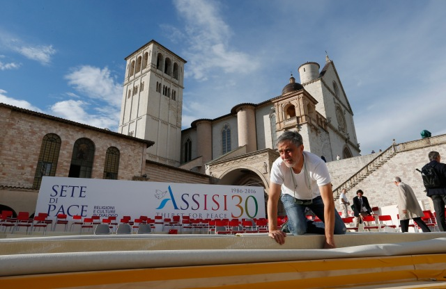 A worker helps prepare the stage for an interfaith peace gathering outside the Basilica of St. Francis in Assisi, Italy, Sept. 19. Pope Francis will attend the Sept. 20 peace gathering marking the 30th anniversary of the first such gathering in Assisi. (CNS/Paul Haring)