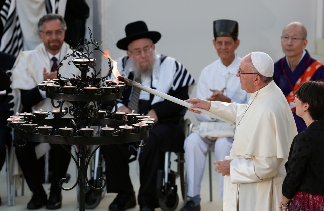 Pope Francis lights a candle during an interfaith peace gathering outside the Basilica of St. Francis in Assisi, Italy, Sept. 20. The pope and other religious leaders were attending a peace gathering marking the 30th anniversary of the first peace encounter. (CNS/Paul Haring)