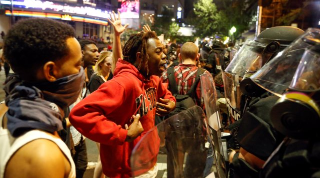 A man confronts riot police during Sept. 21 protests in Charlotte, N.C., after police fatally shot Keith Lamont Scott in the parking lot of an apartment complex. (CNS/Reuters)