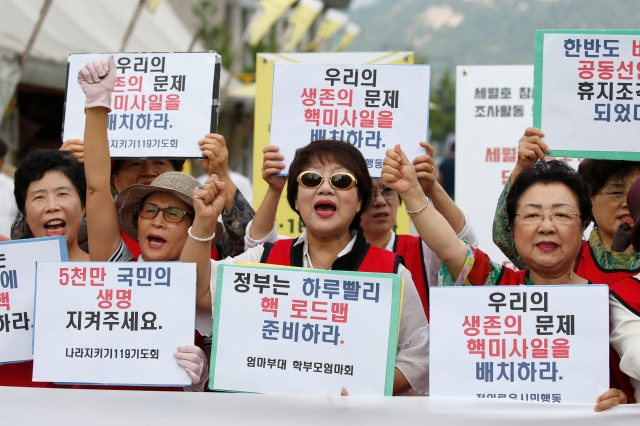 "South Korean activists shout slogans as they hold up banners reading, ""Government needs to prepare the Nuclear Road map for the nation,"" during a Sept 12 protest in Seoul against North Korea's fifth nuclear test. (CNS photo/Jeon Heon-Kyun, EPA)"