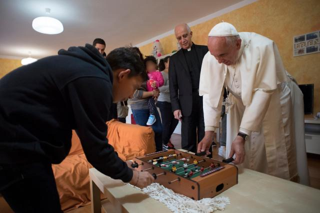 Pope Francis plays table soccer with a young resident during an Oct. 14 visit to Rome's SOS Children's Village. (CNS/L'Osservatore Romano)