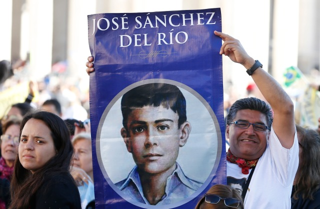 A man holds an image of new Mexican St. Jose Sanchez del Rio, who was martyred at the age of 14 in 1928, before the canonization Mass for seven new saints celebrated by Pope Francis in St. Peter's Square at the Vatican Oct. 16. (CNS/Paul Haring)