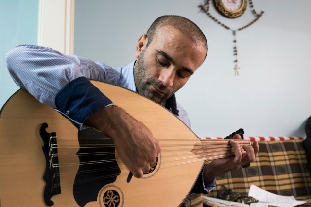 Yako Hanna, a refugee from Iraq, plays a baglama at his home in Istanbul. Hanna completed his application for resettlement to Australia July 21, two years after he landed in Turkey. (CNS/Oscar Durand)