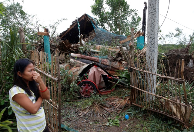 A woman in Bangui, Philippines, stands outside her house damaged by a fallen tree Oct. 20 after Typhoon Haima hit. Heavy damage was reported to homes and farmland in the northern Philippines after the strongest storm in three years struck overnight. (CNS/Reuters)