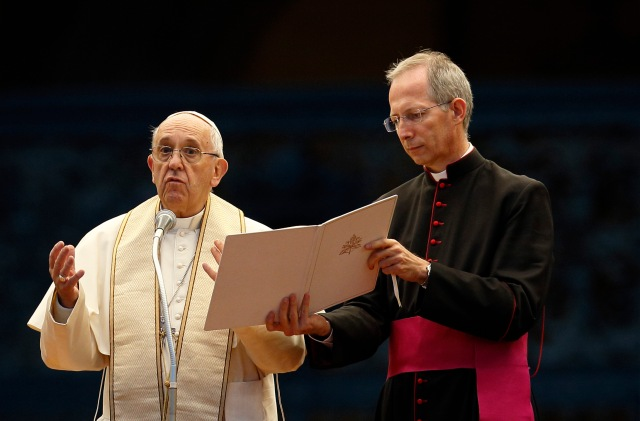 Msgr. Guido Marini, papal master of ceremonies, assists Pope Francis during a Marian vigil in St. Peter's Square at the Vatican Oct. 8. (CNS/Paul Haring)