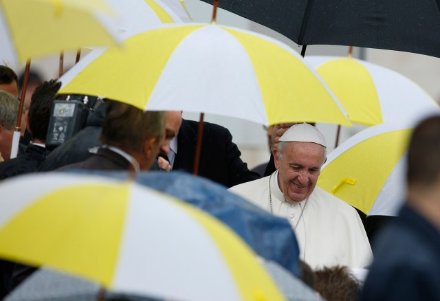 Umbrellas with the Vatican colors are seen as Pope Francis greets the disabled during his general audience in St. Peter's Square at the Vatican Oct. 26. (CNS/Paul Haring)