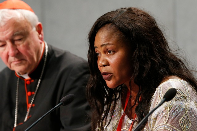 Princess Inyang, who was forced into prostitution by a human trafficker, speaks at a news conference at the Vatican Oct. 27. Also pictured is Cardinal Vincent Nichols of Westminster, England. (CNS/Paul Haring)