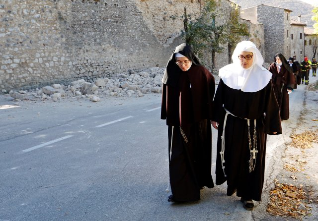 Nuns walk next to a partially collapsed wall Oct. 30 following an earthquake in Norcia, Italy. Thousands of people in central Italy spent the night in cars, tents and temporary shelters following the fourth earthquake in the area in three months. (CNS/Reuters)