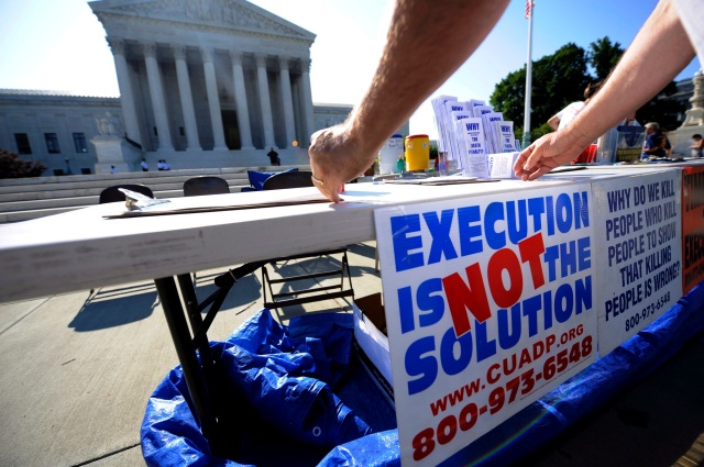 A member of the Abolition Action Committee hangs a sign in front of the Supreme Court in Washington during a 2008 vigil to abolish the death penalty. (CNS photo/Shawn Thew, EPA)