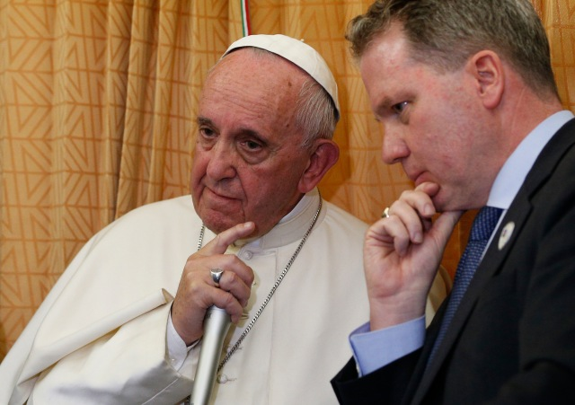Pope Francis and Vatican spokesman Greg Burke listen to a reporter's question aboard a papal flight last year. (CNS/Paul Haring)