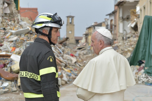 Pope Francis talks with a firefighter as he visits the earthquake-ravaged town of Amatrice, Italy, Oct. 4. (CNS photo/L'Osservatore Romano)