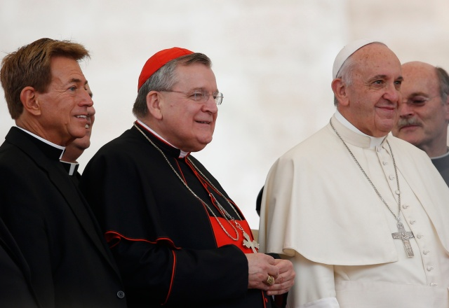 Cardinal Raymond L. Burke, center left, and a group of priests pose with Pope Francis during a papal general audience in 2015. (CNS file/Paul Haring)
