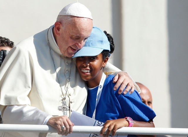 Pope Francis embraces a girl in the popemobile as he arrives for an audience in St. Peter's Square at the Vatican Sept. 3. The audience was for people engaged in the works of mercy and for pilgrims in town for the canonization of Blessed Teresa of Kolkata. (CNS/Paul Haring)