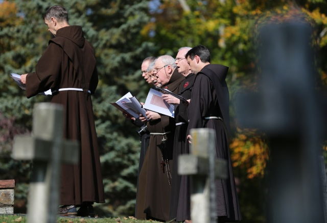 Franciscan friars pray in the cemetery at the Franciscan Monastery of the Holy Land in Washington to mark All Souls' Day Nov. 2. (CNS/Bob Roller)