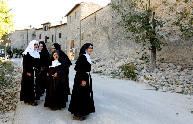 Nuns stand next to a partially collapsed wall Oct. 30 following an earthquake in Norcia, Italy. (CNS/Reuters)
