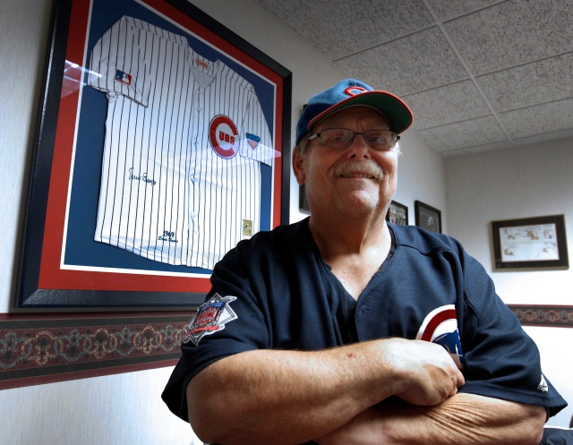 Father John W. Clemens, pastor of Our Lady of Hope Church in Rosemont, Ill., sits near his jersey signed by Chicago Cubs legend Ernie Banks. (CNS/Karen Callaway, Catholic New World)