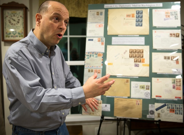 Greg Pirozzi, president of the Vatican Philatelic Society, points out a board displaying some of his Vatican stamps, notes, covers and reference material at his Hanover, Md., home. (CNS/Chaz Muth)