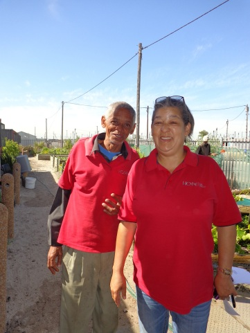 Pauline Jooste, who oversees a South African HIV outreach project with international Catholic funding, walks with Gerald Flagg, a community worker, at the organization's Blikkiesdorp premises near Cape Town. (CNS/Bronwen Dachs)