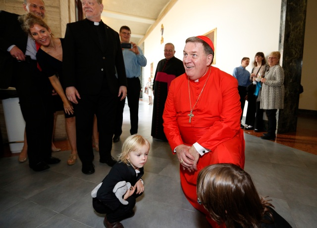 New Cardinal Joseph W. Tobin of Indianapolis gets down to floor level to greet children during a reception at the Pontifical North American College after a consistory at the Vatican Nov. 19. Cardinal Tobin was among 17 new cardinals created by Pope Francis. (CNS photo/Paul Haring)