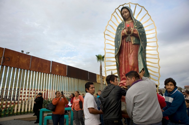 A statue of Our Lady of Guadalupe is unloaded from a truck after a Nov. 19 procession to the U.S.-Mexico border fence in Tijuana, Mexico, where Mass was celebrated. The Mass and a procession with a statue of Our Lady of Guadalupe were a call to remember and pray for migrants. (CNS/David Maung)