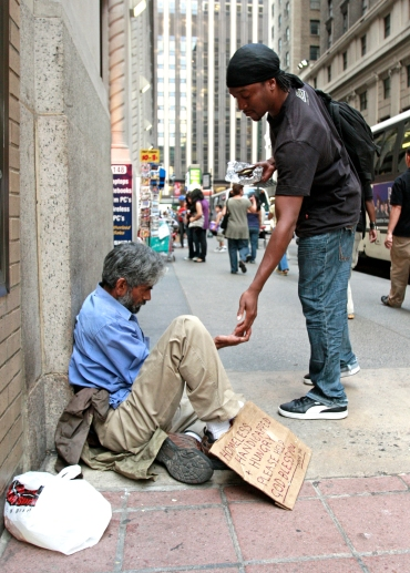 A pedestrian gives money to a homeless man sitting outside St. Francis of Assisi Church in New York City in 2009. (CNS file/Gregory A. Shemitz)