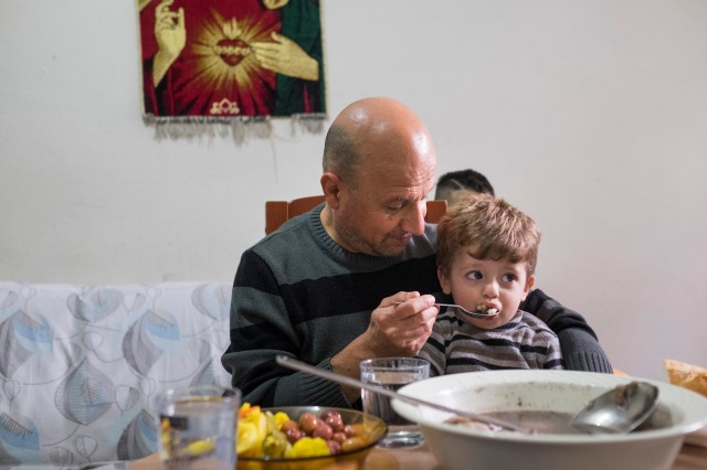 Iraqi refugee Sami Dankha, 51, feeds his son Alin, 1, at his home in Istanbul, Turkey. He lives in Istanbul with his wife and five children; his brothers live in New Zealand, Australia and the Netherlands. (CNS/Oscar Durand)