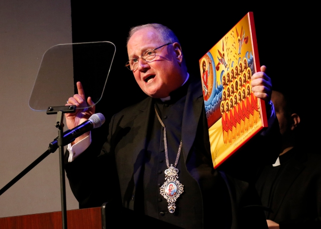 New York Cardinal Timothy M. Dolan holds an icon of the 21 Coptic Martyrs of Libya as he speaks during an interfaith forum on the crisis for Christians in the Middle East at the Sheen Center in New York City Dec. 5. (CNS/Gregory A. Shemitz)