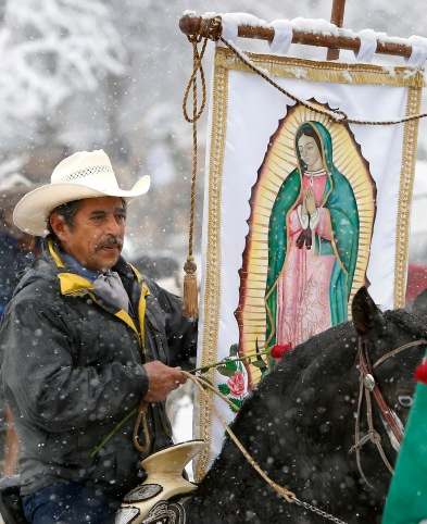 A member of of Club Los Vaqueros Unidos (United Cowboy Club) of Wadsworth, Ill., carries a banner of Our Lady of Guadalupe as he makes his way to the the Shrine of Our Lady of Guadalupe in Des Plaines, Ill., as part of a pre-celebration for her Dec. 12 feast day. (CNS/Karen Callaway, Catholic New World)