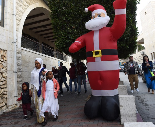 Tourists walk past a large Santa Claus Dec. 17 near the Church of Nativity in Bethlehem, West Bank. (CNS/Debbie Hill)